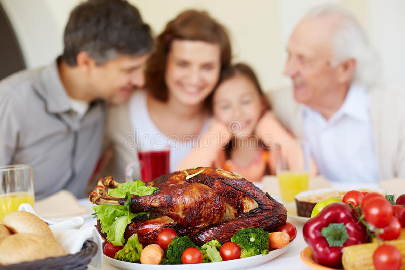 Roasted poultry. Thanksgiving roasted turkey on holiday table and family of four on background stock photography