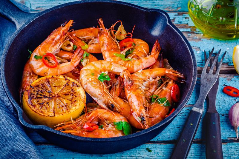 Roasted prawns with parsley, chili pepper, garlic and lemon. Roasted shrimps with parsley, chili pepper, garlic and lemon in frying pan on rustic background royalty free stock photos