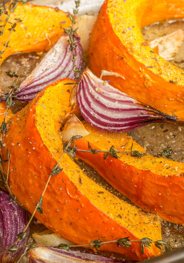 Roasted pumpkin with red onion, garlic and thyme stock photography