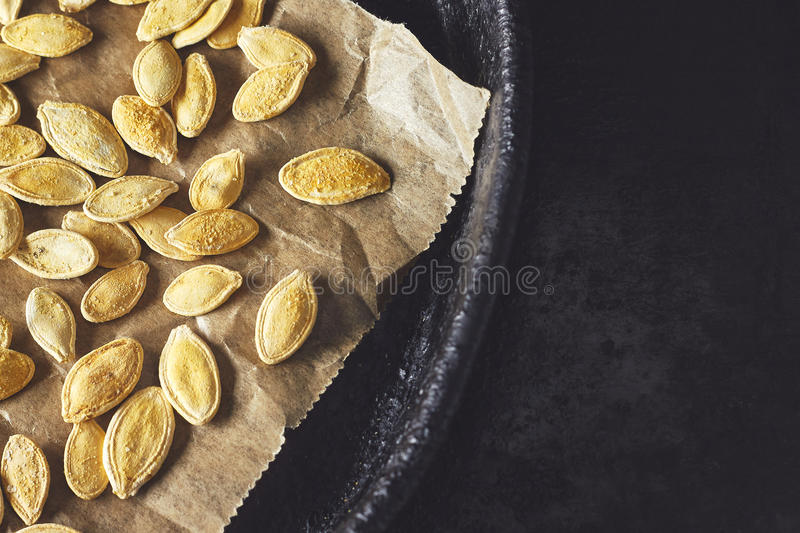 Roasted pumpkin seeds. On black rustic background. Top view with copy space royalty free stock images