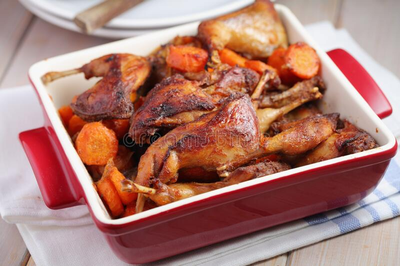Roasted quail legs with carrot and onion royalty free stock photography