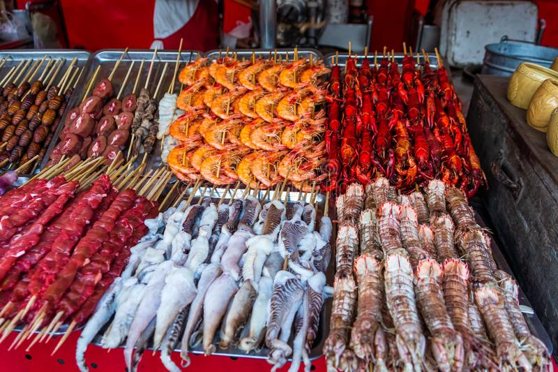 Roasted and raw insects, silkworms, scorpions, bugs, shrimps, crabs, langoustes, snakes, dog meat, on stick royalty free stock images