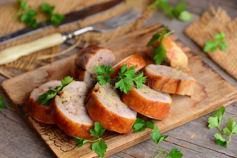 Roasted rellenó los rollos del pollo en un tablero de madera Bifurcación, cuchillo en una tabla de madera Estilo rústico Receta d imagenes de archivo