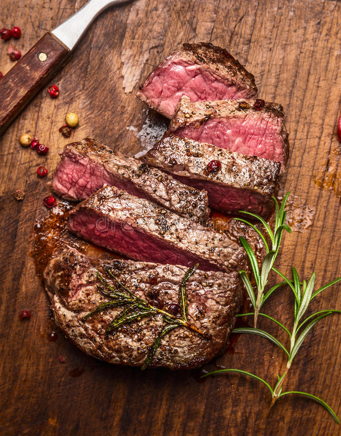 Roasted ribeye steak sliced ​​on a cutting board with a fork ,rosemary and peppers, top view, close up stock photo