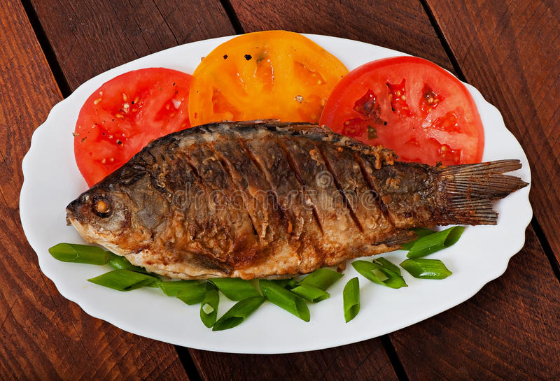 Roasted river fish carp on a white plate. With tomatoes stock photos