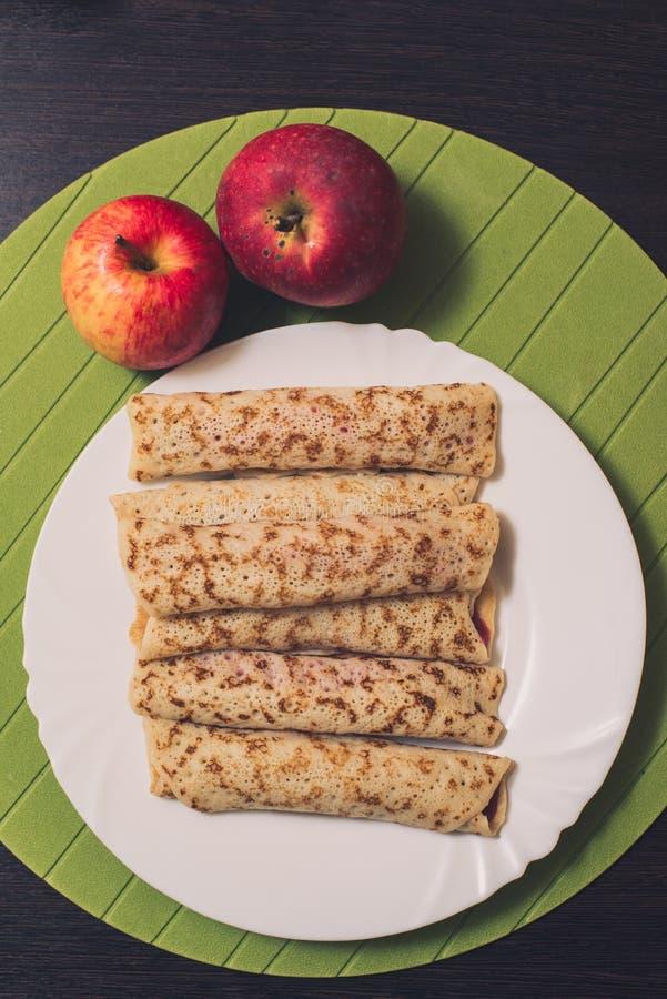 Roasted rodó las crepes en una placa redonda blanca y dos manzanas cerca Visión superior Endecha plana stock de ilustración