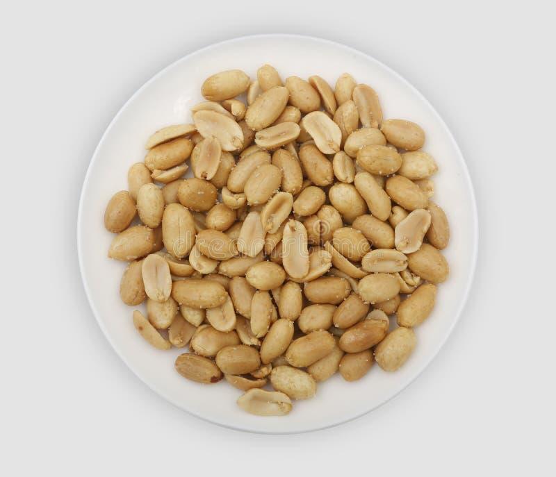 Roasted saló los cacahuetes en una placa blanca imagen de archivo