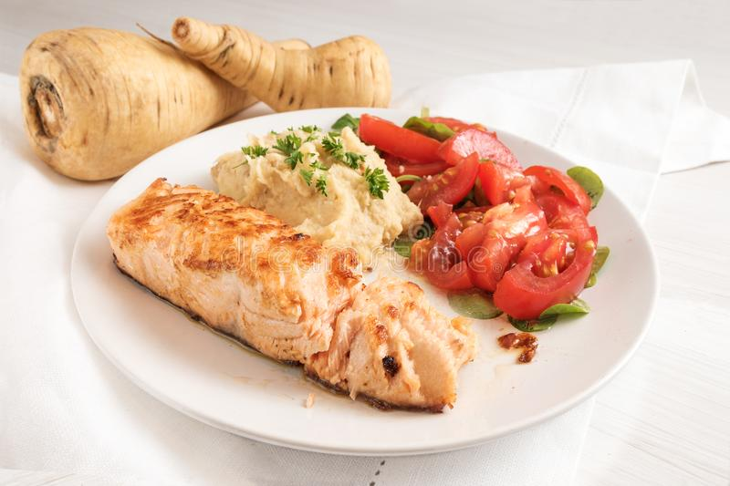 roasted salmon fillet with parsnip puree, tomato salad and parsley garnish, healthy diet meal on a white plate and a white table stock photo