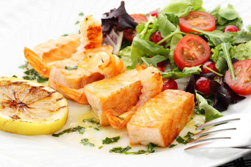 Roasted salmon and shrimps with fresh salad royalty free stock photography