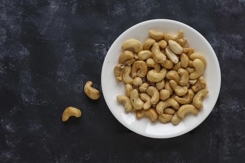 Roasted salted cashew nuts on a white plate stock photo