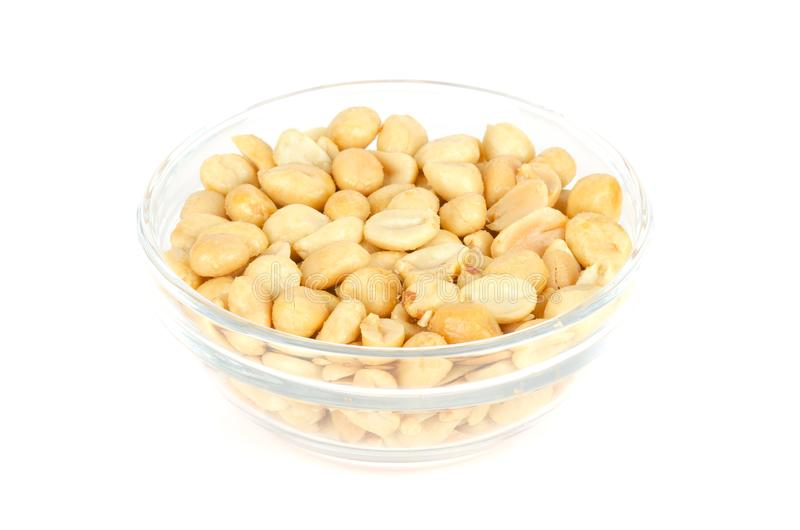 Roasted and salted peanuts in glass bowl over white stock photo
