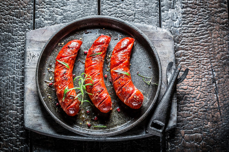 Roasted sausage with fresh herbs on hot barbecue dish. On burnt table stock photography