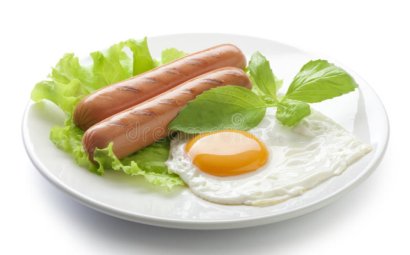 Roasted sausages and fried egg. Two roasted sausages with fried egg, fresh green basil and lettuce on the white plate stock photo