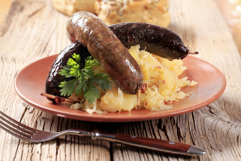 Roasted sausages with sauerkraut and potatoes stock image