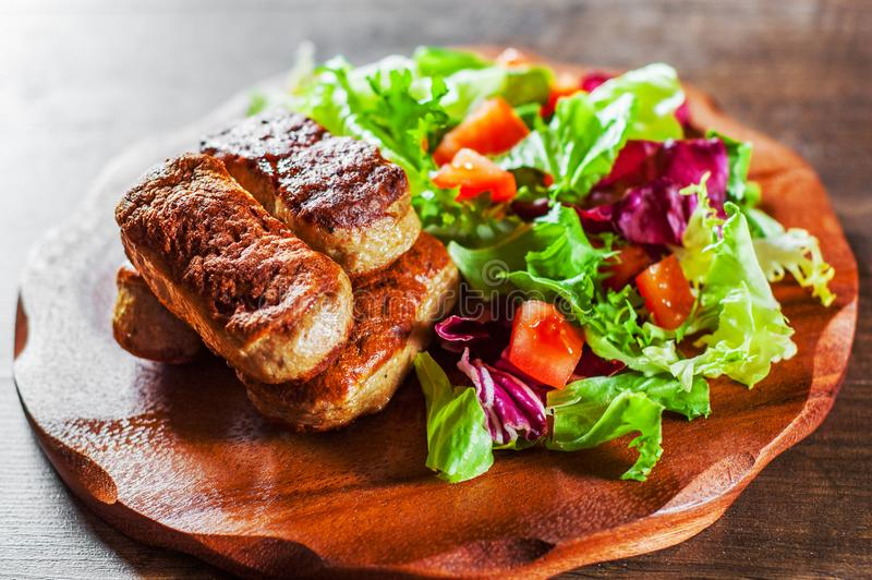 Roasted sausages and various fresh mix salad leaves with tomato in plate on wooden table stock images