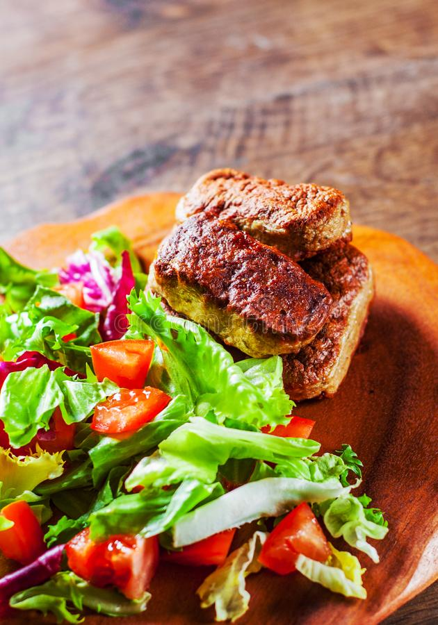Roasted sausages and various fresh mix salad leaves with tomato in plate on wooden table royalty free stock photo