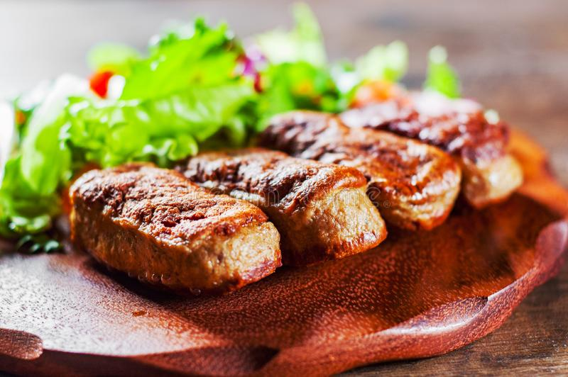 Roasted sausages and various fresh mix salad leaves with tomato in plate on wooden table stock photos