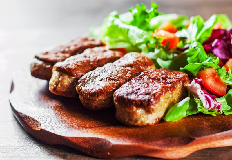 Roasted sausages and various fresh mix salad leaves with tomato in plate on wooden table stock photography