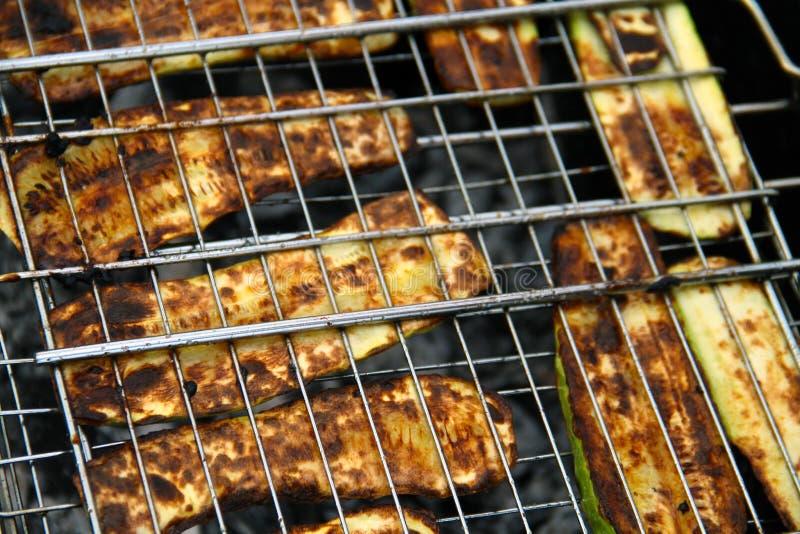 Roasted schnitt Zucchini auf einem Feuer, das in den Reihen auf dem Grill unter brennenden Kohlen ausgebreitet wurde stockfoto