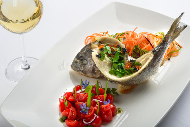 Roasted sea bass. Cherry tomatoes, sliced vegetables herbs stock image