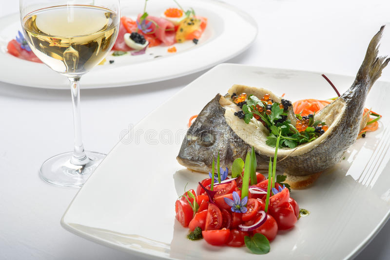 Roasted sea bass. Cherry tomatoes, sliced vegetables herbs royalty free stock photo