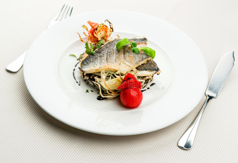 Roasted sea bass. With white and wild rice stock images