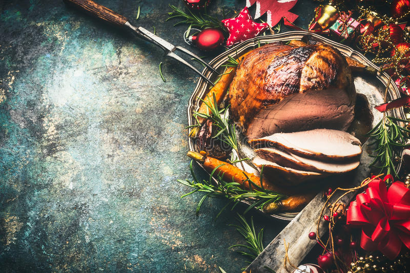 Roasted sliced Christmas ham on festive table background with decoration. Top view royalty free stock photo