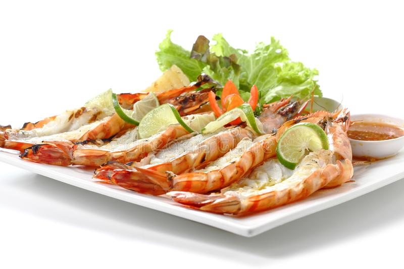 Roasted sliced tiger shrimps with baked potato, slice of lemons, vegetables & chili sauce on square plate, isolated on white royalty free stock image