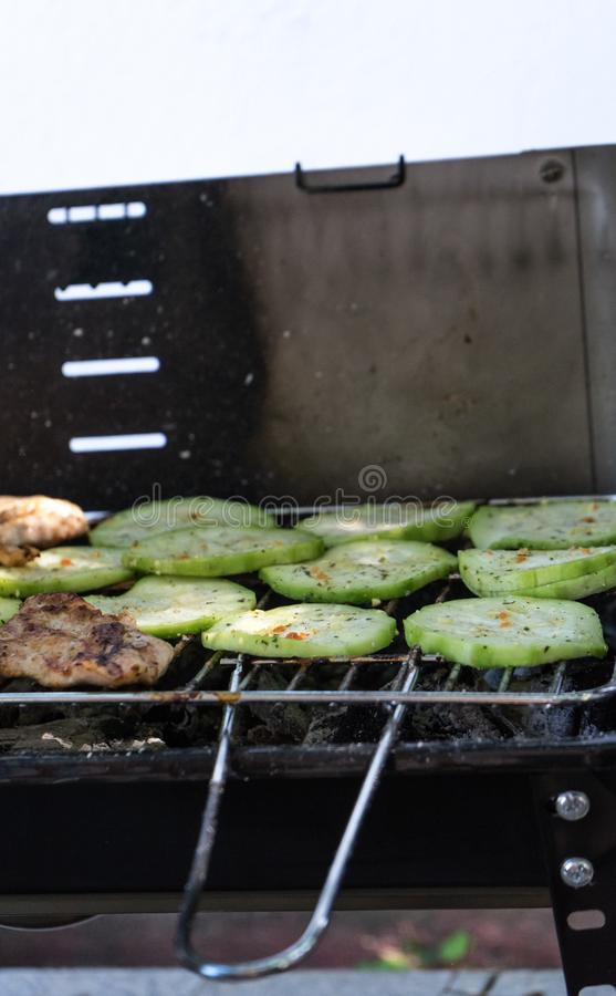 Roasted sliced zucchini on a fire laid out in rows on the grill under burning coals. Meat in barbeque. Chicken steak with. Vegetables are cooked on the BBQ stock photo