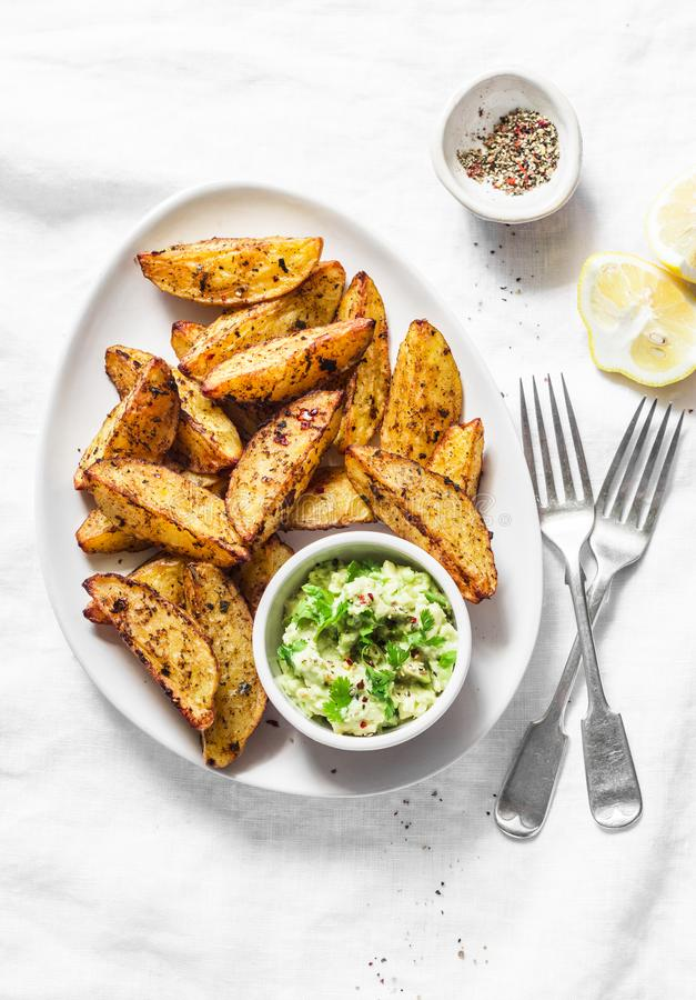 Roasted spices potato with avocado salsa on light background, top view. Tasty snack, tapas or appetizers. Vegetarian food royalty free stock images