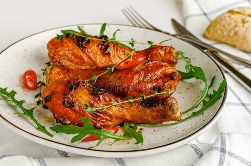 Roasted spicy chicken legs or drumsticks on a white dish. Delicious dinner or lunch royalty free stock images