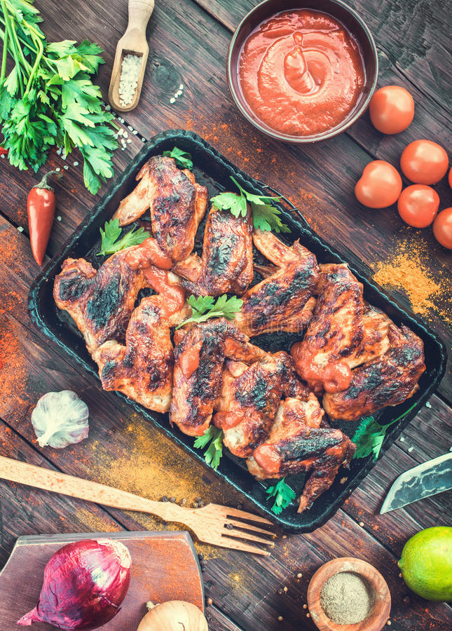 Roasted spicy chicken wings on serving pan. Roasted hot and spicy chicken wings on serving pan. Top view Toned royalty free stock images