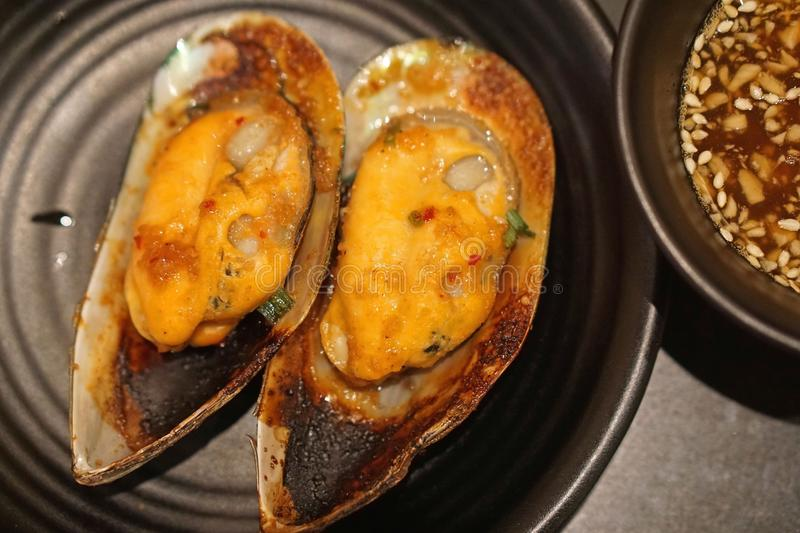 Roasted spicy mussel on black plate royalty free stock photos