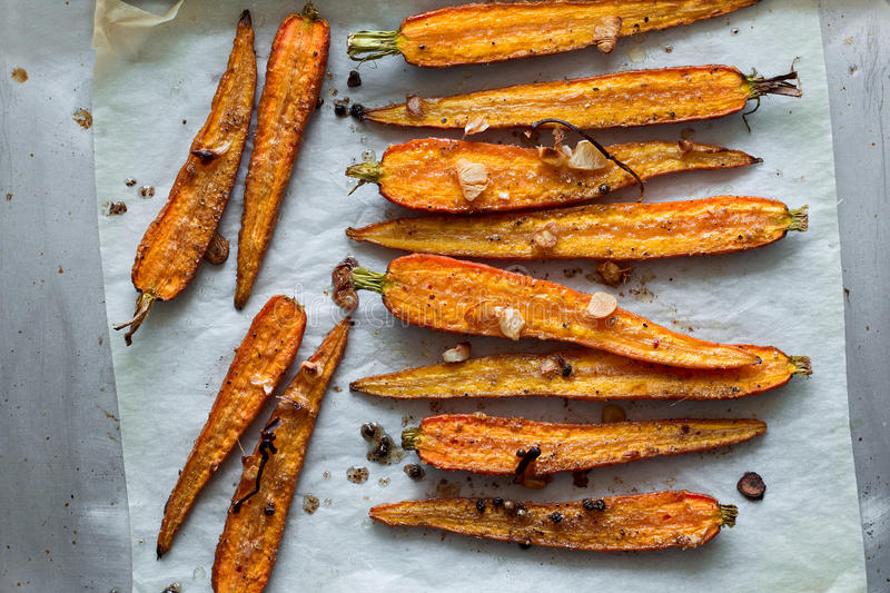 Roasted spring carrots on parchment with garlic, pepper peas and coriander stock photo