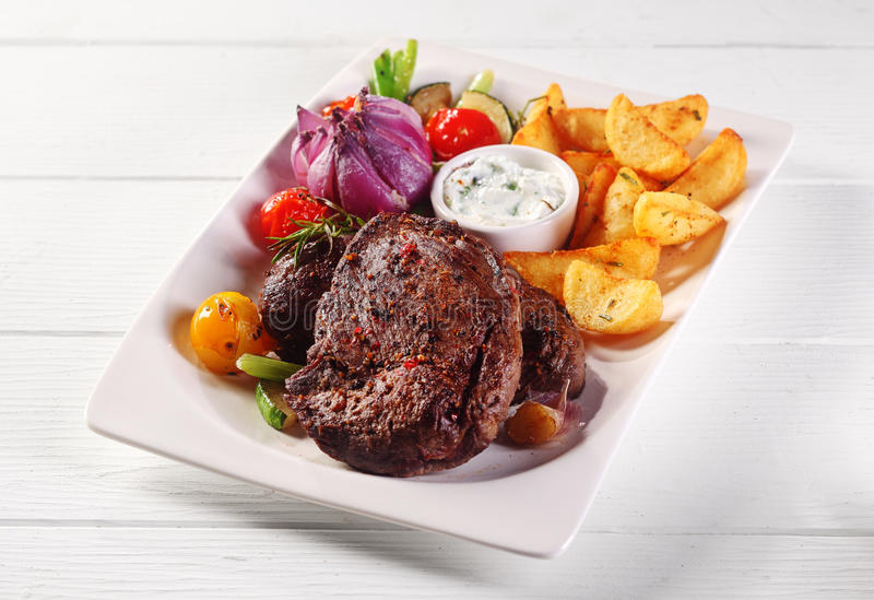 Roasted Steak and Potato Wedges Main Dish. Gourmet Main Dish of Roasted Beef Steak and Potato Wedges on White Plate with Dipping Sauce and Veggies, Served on Top stock photography