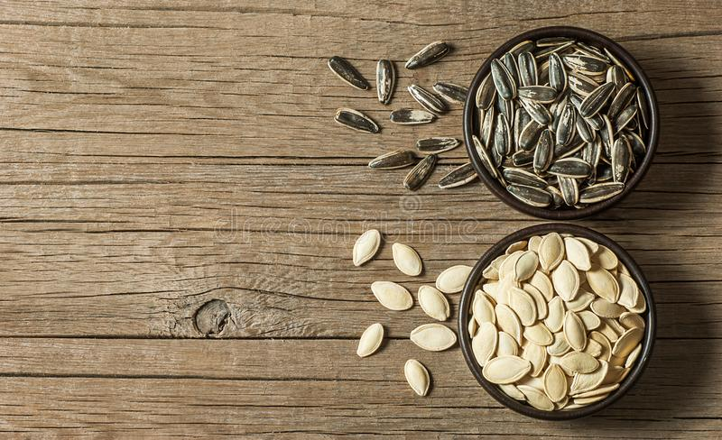 Roasted sunflower seeds and pumpkin seeds in brown bowl on wooden table royalty free stock images