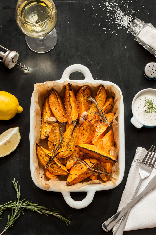 Free Roasted Sweet Potatoes In White Ceramic Dish. Wine, Dip, Lemon, Salt And Rosemary Around Royalty Free Stock Photography - 65519787
