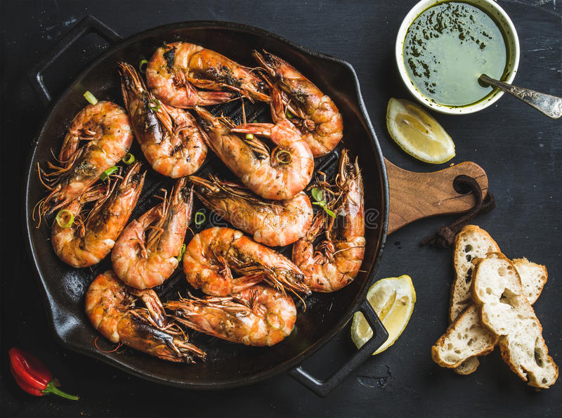 Roasted tiger prawns in iron grilling pan with fresh leek, lemon, bread and pesto sauce over black background stock photography