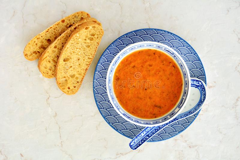 Roasted tomato basil soup top view. Fresh hot homemade roasted tomato basil soup in pretty blue dishes with whole grain bread slices.  Shot from overhead stock images