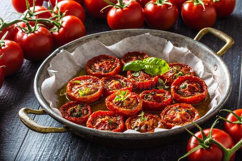 Roasted tomatoes with olive oil thyme oregano and basil in pan stock images
