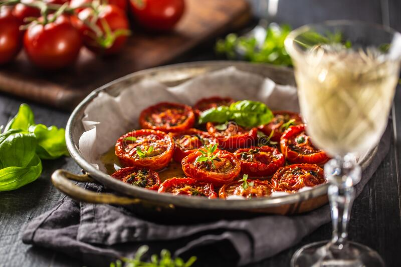Roasted tomatoes with olive oil thyme oregano and basil in pan stock image