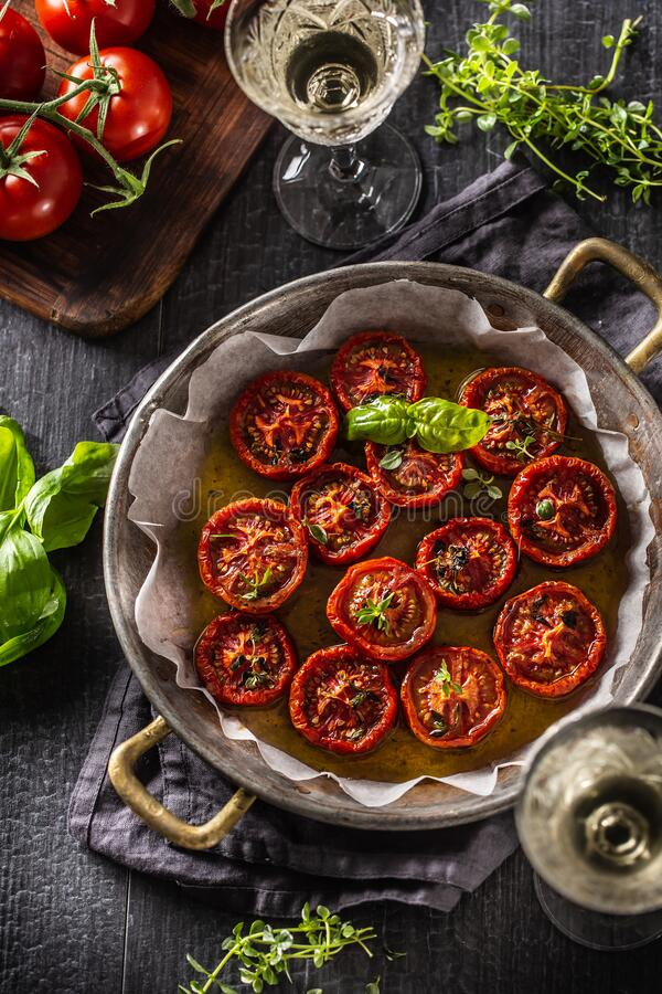 Roasted tomatoes with olive oil thyme oregano and basil in pan royalty free stock photography