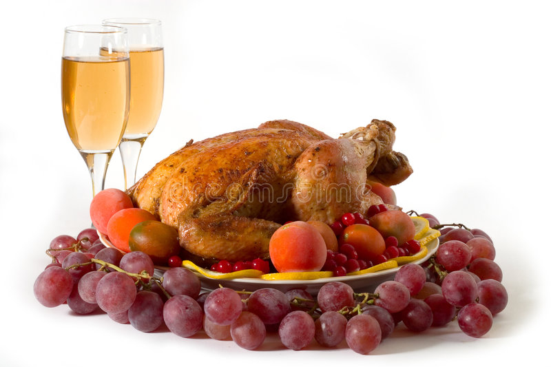 Roasted turkey. Roasted chicken or turkey garnished with lemon, cranberry, apples, tomatoes and wine. Isolated on white royalty free stock images