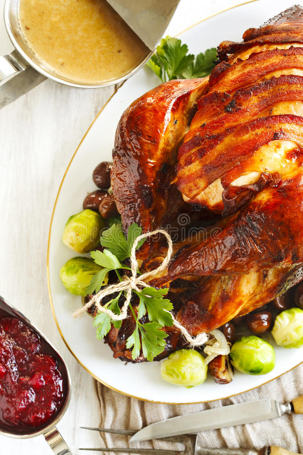 Roasted turkey with bacon and garnished with chestnuts and brussels sprouts. stock photo