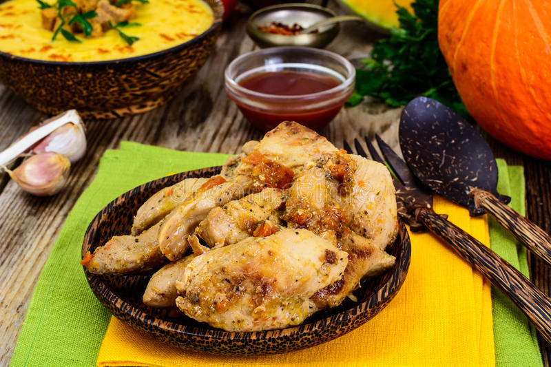 Roasted turkey breast with herbs, pumpkin soup and parsley on Th. Anksgiving Day on old boards stock photo