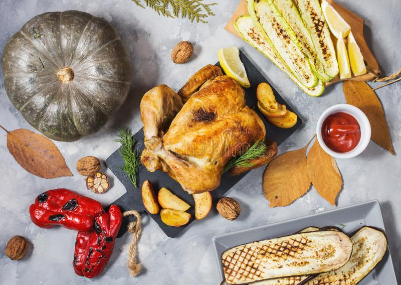 Roasted turkey and grilled zucchini, eggplant and pepper on a rustic concrete table decorated with walnut and autumn leaf. Flat la stock image