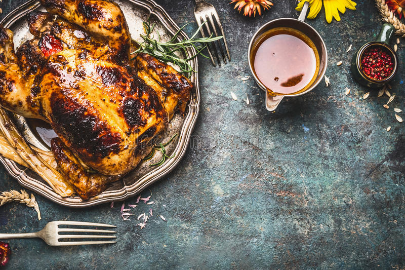 Roasted turkey with sauce served for Thanksgiving dinner on rustic table background stock photos