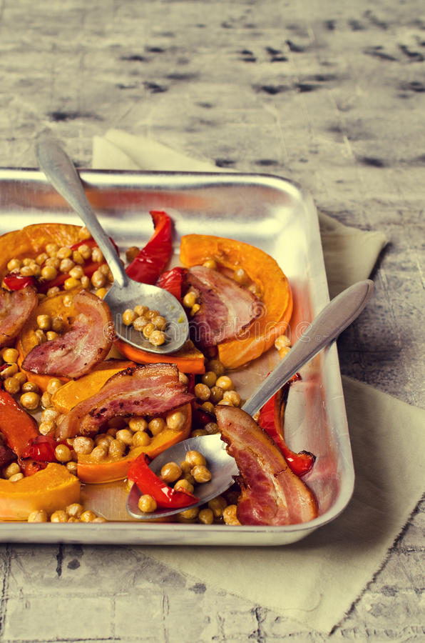 Roasted vegetables with bacon. And chickpeas. Selective focus royalty free stock image