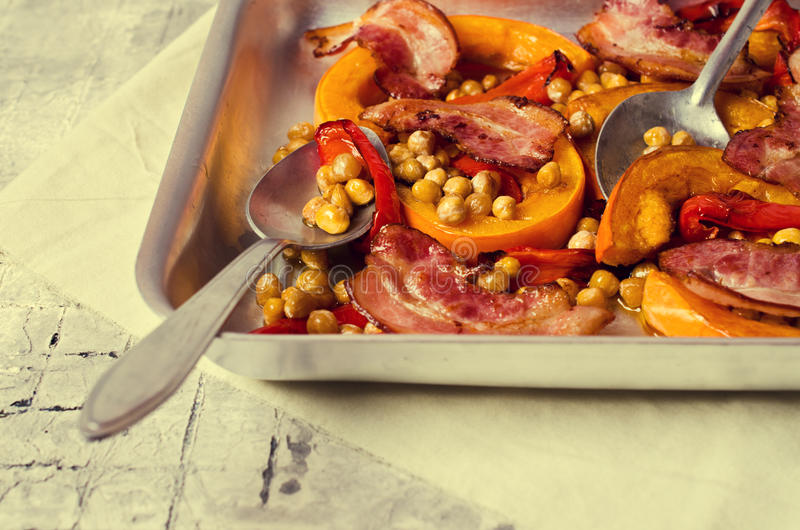 Roasted vegetables with bacon. And chickpeas. Selective focus royalty free stock photography