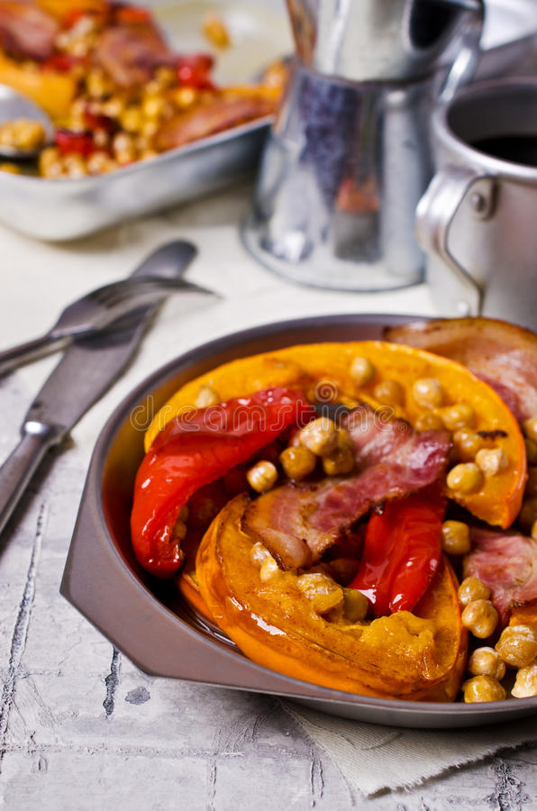 Roasted vegetables with bacon. And chickpeas. Selective focus royalty free stock images